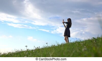 Beautiful brunette girl in black dress standing on grassy hill and making photos with her phone. 4K video