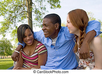 three friends in the park - small group of 3 multi-ethnic...