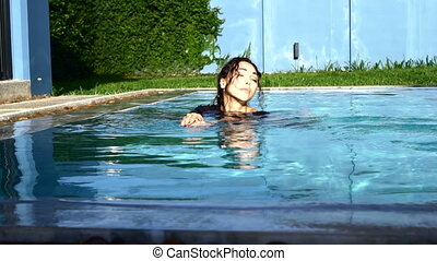 Beautiful brunette woman in the outdoor pool
