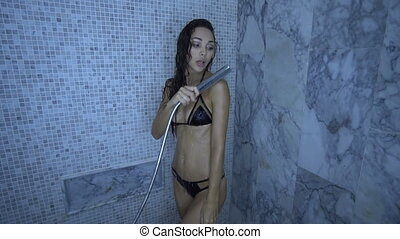 Woman in bikini taking shower after spa treatments -...