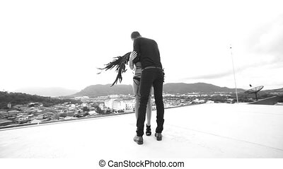 Man kissing black angel woman on the rooftop