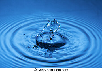 Water drop falling down. Abstract blue background.