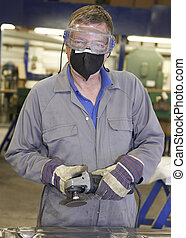 Worker with angle grinder - factory floor worker holding a...