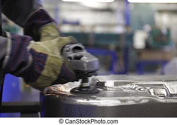 Worker with angle grinder - man using a angle grinder on...