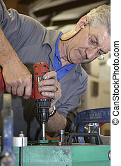 worker and hand drill - worker on factory floor using...