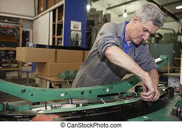 factory floor worker - senior worker on factory floor in the...