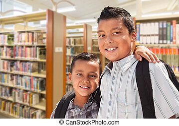 Young Hispanic Student Brothers In Library - Happy Young...