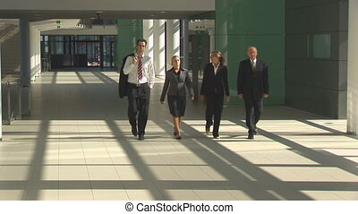 taff businessteam walking - four businesspeople walking in...