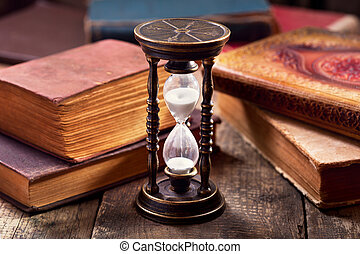 old hourglass with books