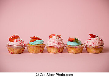 Colorful cupcakes decorated with sprinkles and strawberries...