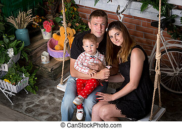 Portrait of happy family with baby boy posing on swing at...
