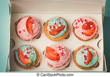 Closeup of six decorated cupcakes in paper gift box -...