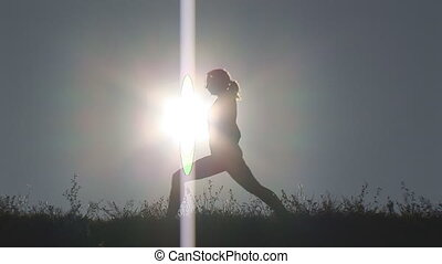 woman in lunge - woman exercising in lunge on hill at late...