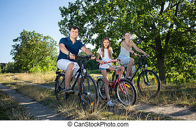 Girl riding with parents on bicycles in meadow at sunny day....