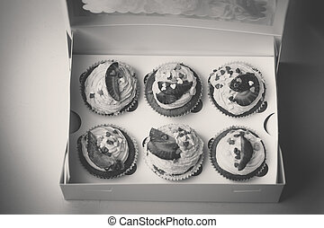 Black and white photo of open box with 6 cupcakes with...