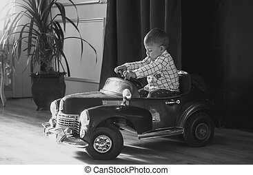 Black and white image of 1 year old boy riding big toy car -...