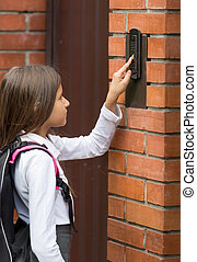 Closeup image of cute schoolgirl ringing in doorbell -...