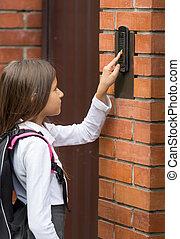 Closeup image of cute schoolgirl ringing in doorbell