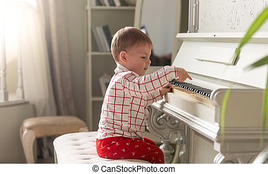 Toned portrait of adorable baby boy playing the piano -...