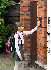 Schoolgirl with rucksack ringing in doorbell - Cute...