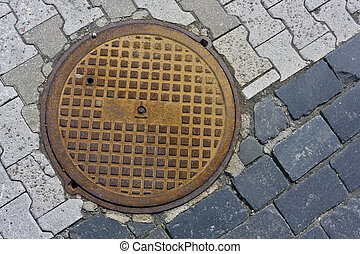 hatch of the city sewerage - Round rusty pig-iron hatch of...