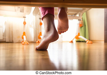 Closeup of female feet under the bed on wooden floor -...