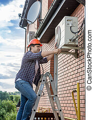 Young technician repairing outside air conditioning unit -...