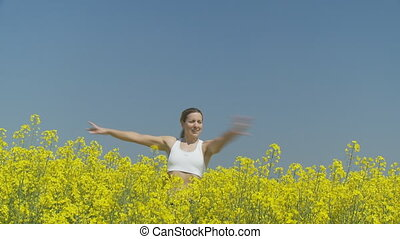 happy young woman in rape field - smiling woman turning in...