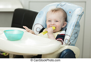 Portrait of smiling baby boy eating with spoon - Portrait of...