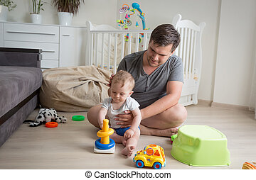 Father sitting on floor with his baby boy and playing with...
