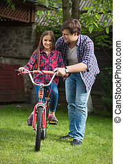 Young man teaching girl how to ride a bicycle at park