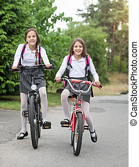 Happy girls in uniform riding to school at morning