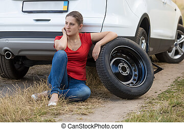 Woman sitting next to the car with flat tire and waiting for help