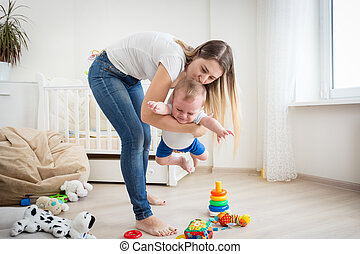 Cheerful mother playing with her baby boy at living room