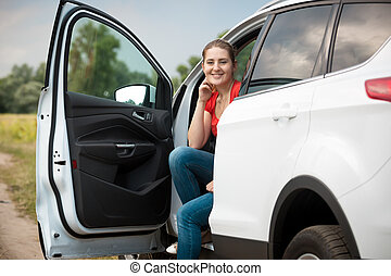 Portrait of smiling female driver relaxing in car at the...
