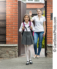 Smiling girl going out the house to school Mother standing...