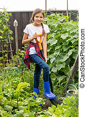 Happy girl working at garden with shovel