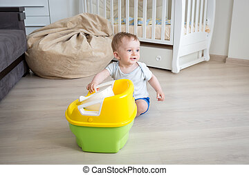 Adorable baby boy playing with chamber pot at living room