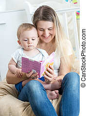 Beautiful cheerful mother reading book with her baby boy -...