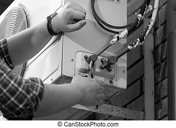 Black and white photo of electrician repairing air...