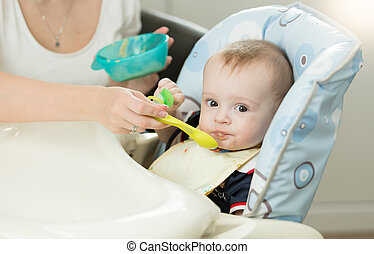 Closeup of young mother feeding baby boy in highchair -...
