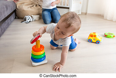Adorable baby crawling on floor and assembling colorful toy tower