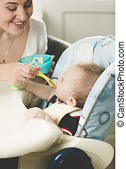 Happy young mother feeding her baby in highchair from spoon