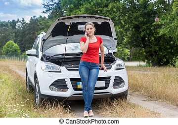 Frustrated woman leaning on broken car in field and calling...