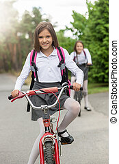Portrait of smiling girl in school uniform riding bicycle -...