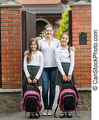 Smiling mother standing in doorway with two daughters leaving for school