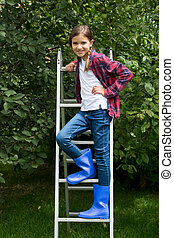Little girl in blue gumboots standing on stepladder at apple...