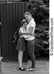 Black and white image of mother seeing off her daughter...