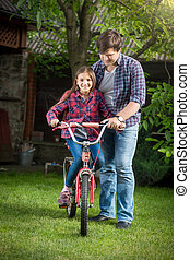 Smiling girl learning how to ride a bicycle with her father at park