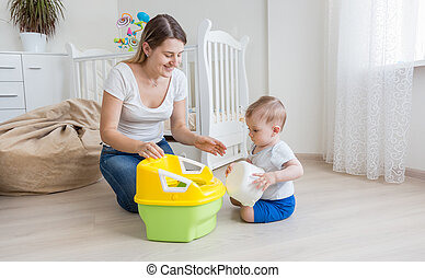 loving mother teaching her baby boy how to use chamber pot -...